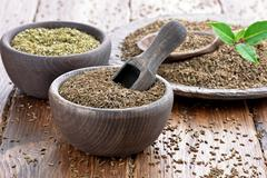 Cumin with marjoram in wooden bowls Stock Photos