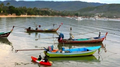 People swim in the kayak next to fishing boats Stock Footage