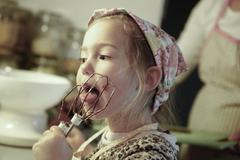 Little girl licking chocolate off the mixer beater Stock Photos