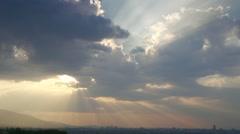 The sun penetrates spectacular between clouds and sun illuminate town Stock Footage