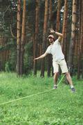 Sport, leisure, recreation and healthy active lifestyle concept - man slackli Stock Photos