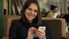 Portrait of happy, pretty woman with smartphone sitting in cafe in city Stock Footage