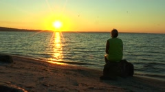 A woman looking at the sunrise over the sea - stock footage