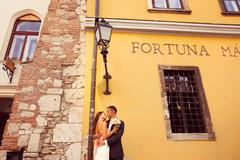 Stock Photo of Bride and groom posing near old house
