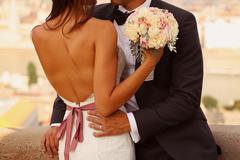 Detail of a bride and groom embracing. Bride holding beautiful wedding bouque Stock Photos