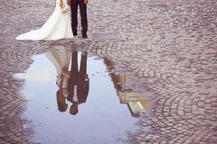 Bride and groom reflected in slop on paved road Stock Photos