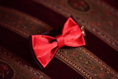 Red bowtie on striped background - stock photo