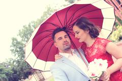 Stock Photo of Beautiful couple with red umbrella on a rainy day