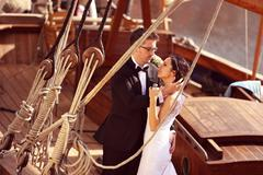 Bride and groom embracing near big ship with strings - stock photo