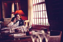 Bride and groom at restaurant, in a warm atmosphere Stock Photos