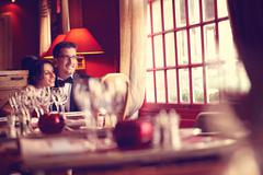 Bride and groom at restaurant, in a warm atmosphere - stock photo