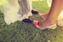 Feet of bride and groom on grass - stock photo