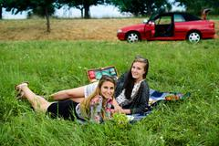 Best friends having a picnic next to their car - stock photo