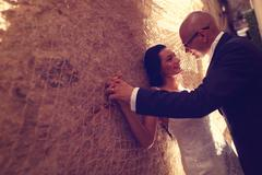 Bride and groom against a wall with trammel - stock photo