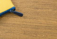 Yellow Pocket Bag and Blue Zipper on Wooden Table with Copy Space for Text De - stock photo