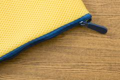 Yellow Pocket Bag and Blue Zipper on A Wooden Table. - stock photo