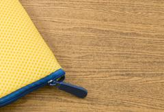 Yellow Pocket Bag and Blue Zipper on A Wooden Table with Copy Space for Text Stock Photos