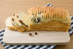 Cuisine and Food, Delicious Sliced Brown Raisin Bread on Wooden Cutting Board - stock photo