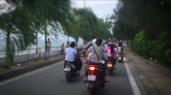 Handheld POV shot of Scooters in an Asian city drive along a lake in traffic Stock Footage