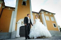 Newlyweds posing in front of castle - stock photo