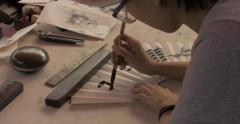 4K Calligrapher Writes on Paper Fan Stock Footage