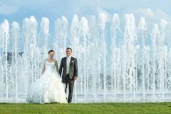 Bride and groom in front of water spray fountain Stock Photos