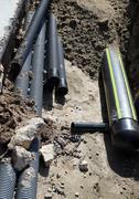 Stock Photo of pipes and a big gas pipeline inside the excavation in road construction