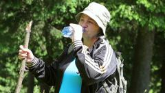 Senior tourist woman drinking water in the forest Stock Footage