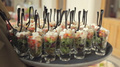 Stock Video Footage of Waiter puts vegetable salad in individual containers on the table at banquet