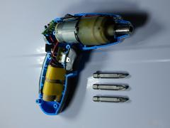Disassembled electric screwdriver cutaway and set of nozzles Stock Photos