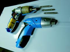 Disassembled electric screwdriver cutaway and set of nozzles detailed - stock photo