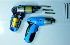 Disassembled electric screwdriver cutaway and set of nozzles - stock photo