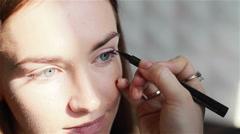 Professional make-up artist applying eyeliner. Drawing winged eyeliner. Close-up Stock Footage
