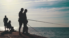 Men fishing on pier at the beautiful sunrise, silhouette Stock Footage