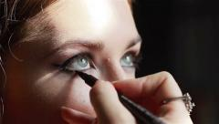 Professional make-up artist applying winged eyeliner. Close-up Stock Footage