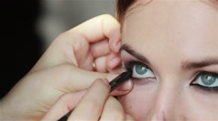 Professional make-up artist lining inner rim of the eye. Eyeliner make-up. Close - stock footage