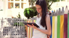 Schoolgirl using tablet pc in front of the school Stock Footage