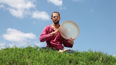 Young man playing the tambourine on blue sky background - stock footage