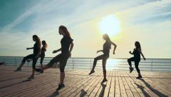 Zumba class dancing  at the sunrise near the beach. slow motion, steadycam shot - stock footage