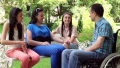Young man in wheelchair with family in the park Stock Footage