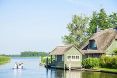 Little house staying on the river and visitors  in Giethoorn Stock Photos