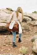 Stock Photo of Woman walking past rocks in a desert, carrying a leather bag.