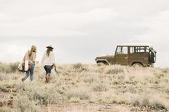 Two women walking towards a 4x4 parked in a desert. - stock photo