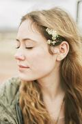 Head and shoulders portrait of a woman with a flower in her hair. - stock photo