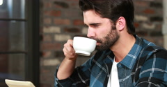 Smiling hipster man using a tablet and sipping coffee Stock Footage