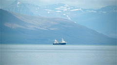 Trawler fishing ship sails through snow capped mountain fjord, Iceland - stock footage