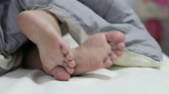 Two feet relax in a bed. Stock Footage