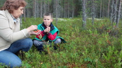 Mature mother holding fresh cloudberries in hands while boy eating it Stock Footage