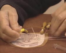 Close up old lady's hands, making bobbin lace, using a pattern Stock Footage