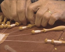 Old lady's hands, making bobbin lace, weaving the bobbins - close up Stock Footage